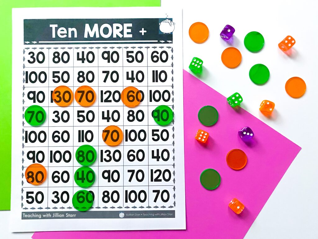 A math Halloween center where students roll dice and then add ten more to the sum. The game board, counters and dice are visible for this Halloween center.