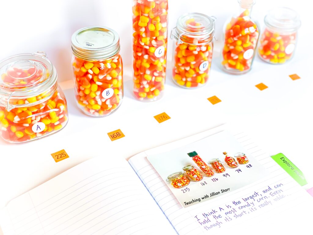 Estimation Halloween Center. 6 jars of different sizes filled with Halloween candy are in a line with a student math journal open to begin writing.